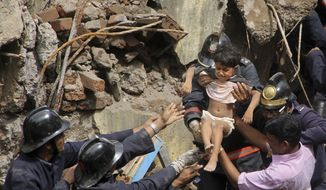 Indian Fire officials rescue a girl from debris of a collapsed building in Mumbai, India, Friday, Sept. 27, 2013. The multistory residential building collapsed in India's financial capital of Mumbai early Friday, killing at least three people and sending rescuers racing to reach dozens of people feared trapped in the rubble. (AP Photo)