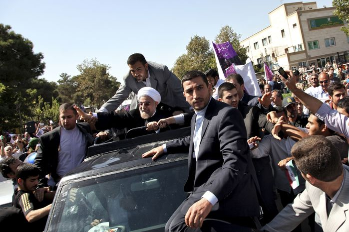 Iranian President Hassan Rouhani, center, waves to supporters upon his arrival from the US near the Mehrabad airport in Tehran, Iran, Saturday, Sept. 28, 2013. Iranians from across the political spectrum hailed Saturday the historic phone conversation between President Barack Obama and Rouhani, reflecting wide support for an initiative that has the backing of both reformists and the country's conservative clerical leadership. (AP Photo/Ebrahim Noroozi)