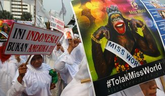 Muslim women hold posters reading: Indonesia is not America, left, and Reject Miss World, during a protest demanding the cancellation of the Miss World pageant, in Jakarta, Indonesia, Sept. 6. 2013. (AP Photo/Dita Alangkara)