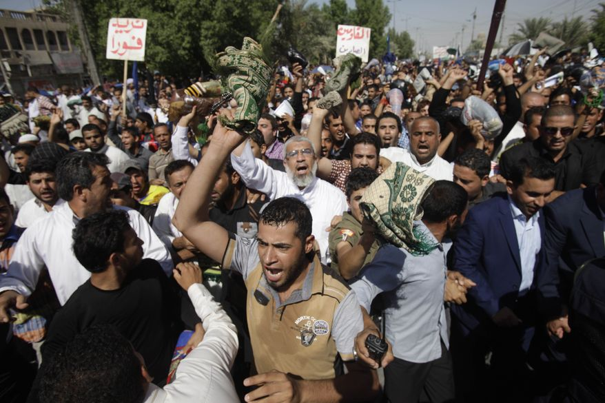 Iraqi followers of Shiite cleric Muqtada al-Sadr hold a demonstration in the Sadr City neighborhood of Baghdad on Friday, Sept. 27, 2013, to call for the release of detainees held by Iraqi authorities. (AP Photo/Karim Kadim)