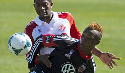 Toronto FC defender Donel Henry, rear, and D.C. United forward Michael Seaton battle for a ball during the first half of an MLS soccer game against Toronto FC in Toronto on Saturday June 28, 2013. (AP Photo/The Canadian Press, Frank Gunn)