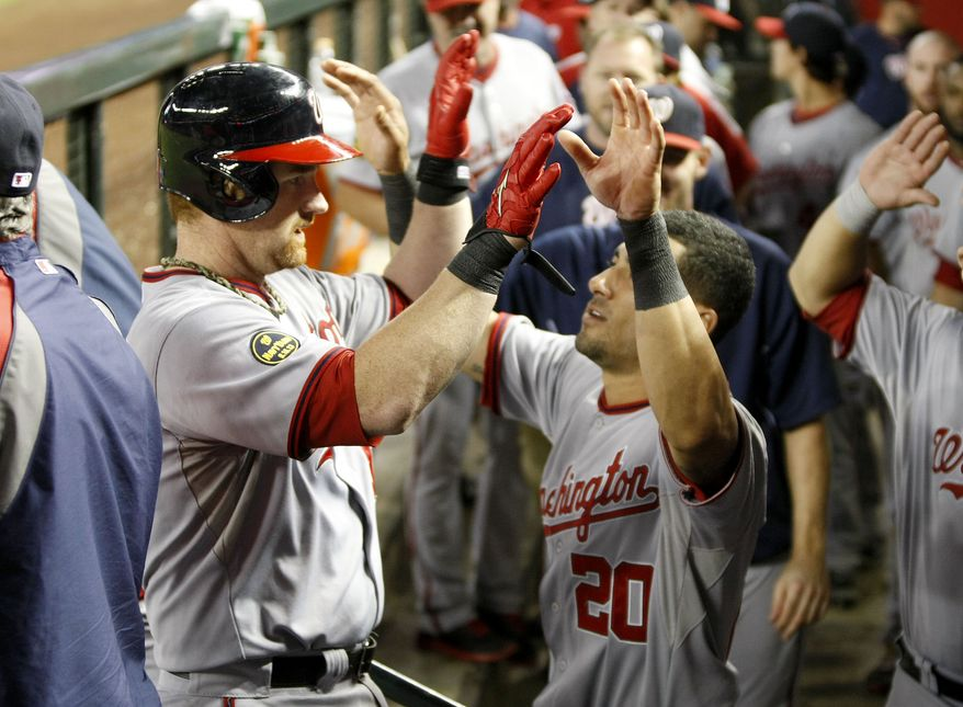 Washington Nationals' Chad Tracy, left, is congratulated by teammate Ian Desmond (20) as he returns to the dugout following his solo home run off Arizona Diamondbacks pitcher Brandon McCarthy during the seventh inning of a baseball game on Saturday, Sept. 28, 2013, in Phoenix. (AP Photo/Ralph Freso)