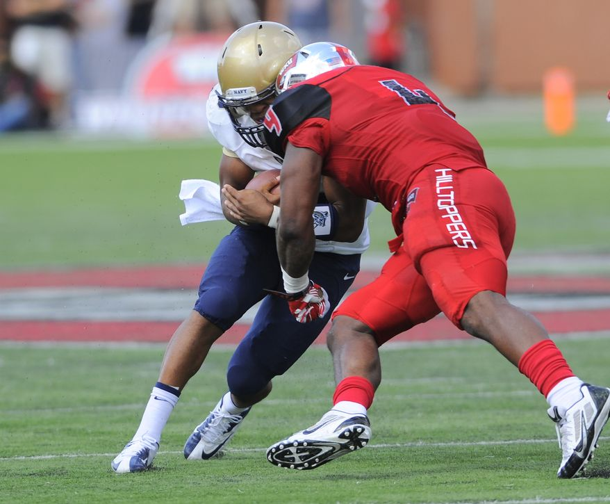 Western Kentucky Hilltoppers linebacker Andrew Jackson (4) hits Navy Midshipmen quarterback Keenan Reynolds (19) during the first half of an NCAA college football game on Saturday, Sept. 28, 2013, in Bowling Green, Ky. Reynolds would leave the game and not return after the hit. (AP Photo/Joe Imel)