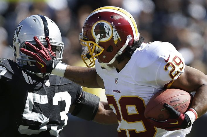 Washington Redskins running back Roy Helu stiff-arms Oakland Raiders linebacker Nick Roach (53) during the second quarter of an NFL football game in Oakland, Calif., Sunday, Sept. 29, 2013. (AP Photo/Marcio Jose Sanchez)