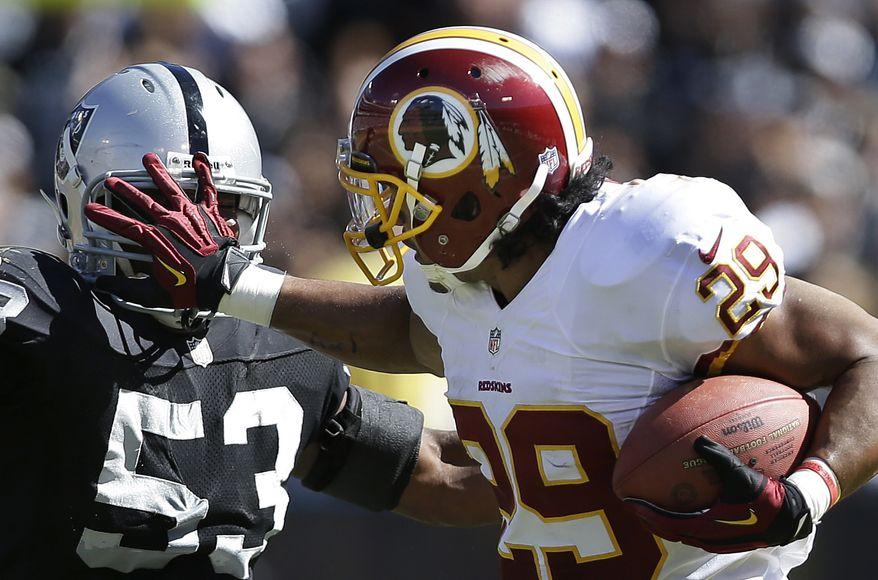 Washington Redskins running back Roy Helu stiff-arms Oakland Raiders linebacker Nick Roach (53) during the second quarter of an NFL football game in Oakland, Calif., Sunday, Sept. 29, 2013. (AP Photo/Marcio Jose Sanchez)