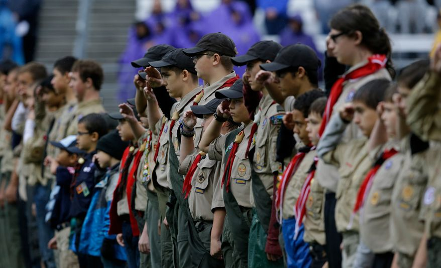 Boy Scouts salute the flag before an NCAA college football game between Arizona and Washington, Saturday, Sept. 28, 2013, in Seattle. (AP Photo/Ted S. Warren)