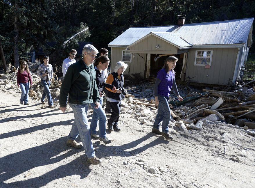 Senator Mark Udall, at left, walks through the flood damage with Jamestown mayor Tara Schoendinger, and Boulder County Commissioners Deb Gardner and Elise Jones in Jamestown on Saturday, Sept. 28, 2013. (AP Photo/Daily Camera, Jeremy Papasso)
