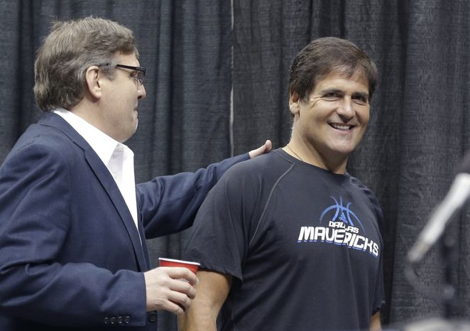 ** FILE ** Dallas Mavericks owner Mark Cuban (right) gets a pat on the back from Donn Nelson, president of basketball operations, before a news conference in Dallas on Thursday, Aug. 15, 2013. The government's insider-trading case against Cuban goes to trial on Monday, Sept. 30, 2013, in federal court in Dallas. (AP Photo/LM Otero)
