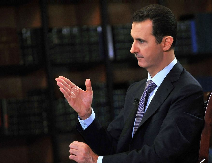 Syrian President Bashar Assad gestures as he speaks during an interview with Italy's RAI News 24 TV at the presidential palace in Damascus, Syria, on Sunday, Sept. 29, 2013. Mr. Assad said his government will abide by last week's U.N. resolution calling for the country's chemical weapons program to be dismantled and destroyed. (AP Photo/SANA)