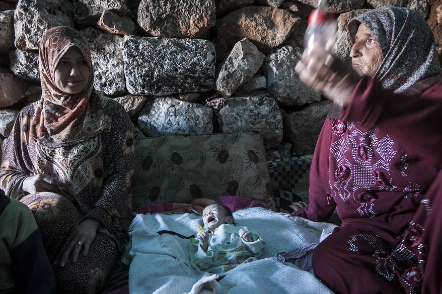 ** FILE ** Displaced Syrian women sit with 1-month-old Fatima on Friday, Sept. 27, 2013, inside a stone house near Kafer Rouma, in ancient Roman ruins used as temporary shelter by refugees from the heavy fighting and shelling in the Idlib province countryside of Syria. (AP Photo)