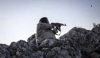 A Syrian opposition fighter aims at government forces during exchange of fire in Telata, a front-line village at the top of a mountain in the Idlib province of Syria. (AP Photo)