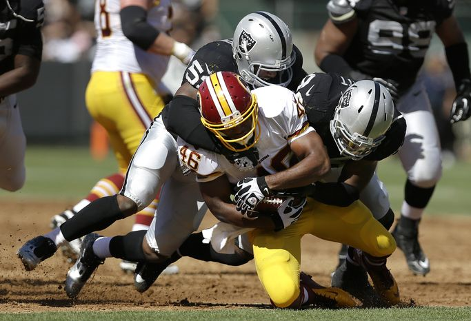 Washington Redskins running back Alfred Morris (46) is tackled by Oakland Raiders linebacker Nick Roach, top, and outside linebacker Kevin Burnett during the first half of an NFL football game in Oakland, Calif., Sunday, Sept. 29, 2013. (AP Photo/Marcio Jose Sanchez)