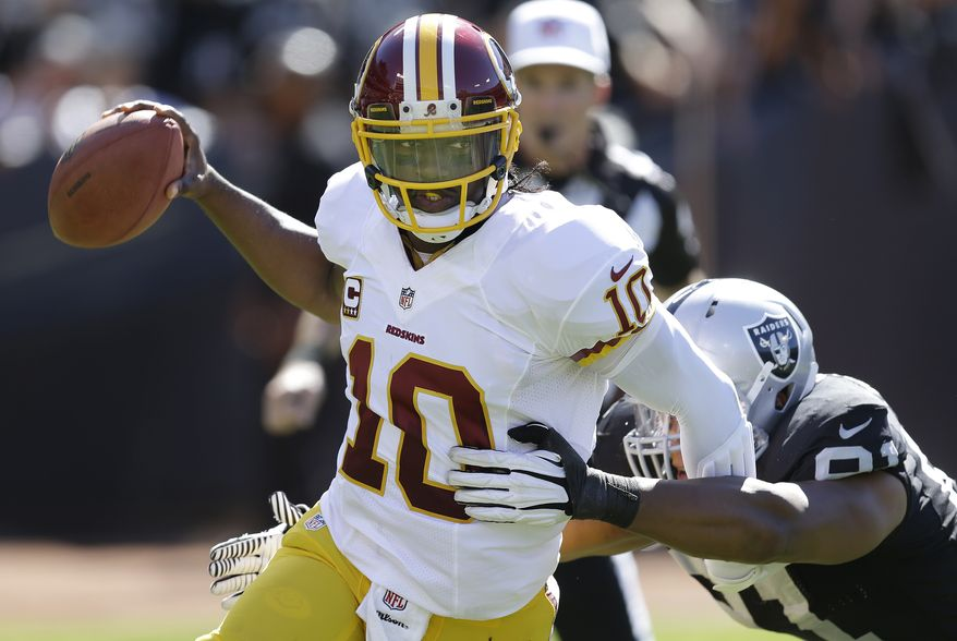 Washington Redskins quarterback Robert Griffin III (10) runs from Oakland Raiders defensive end Jack Crawford (91) during the second quarter of an NFL football game in Oakland, Calif., Sunday, Sept. 29, 2013. (AP Photo/Ben Margot)