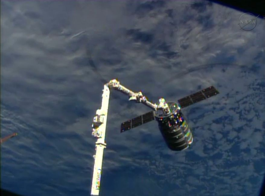 This frame-grabbed image provided by NASA-TV shows the Cygnus spacecraft attached to the Canadarm 2 on the International Space Station on Sunday Sept. 29, 2013. At the time, both vehicles were traveling over the Indian Ocean. (AP Photo/NASA-TV)