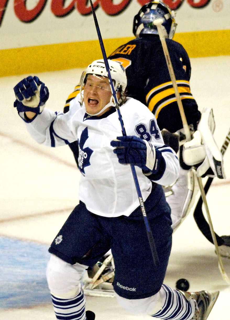 Toronto Maple Leafs center Mikhail Grabovski celebrates after a goal against Buffalo Sabres goalie Ryan Miller, top, late in the third period to tie the NHL hockey game in Buffalo, N.Y., Friday, Oct. 30, 2009. Buffalo won in overtime 3-2.  (AP Photo/Don Heupel)