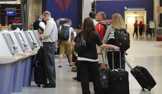 In this Friday, Sept. 27, 2013, photo, Delta Air Lines passengers line up to check luggage at Hartsfield-Jackson Atlanta International Airport, in Atlanta.  Delta customers now have the option to purchase an upgrade that includes a second bag to check, amongst other perks. (AP Photo/John Amis)
