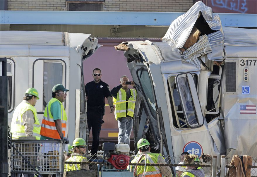 Authorities inspect the wreckage of two Chicago Transit Authority trains that crashed Monday, Sept. 30, 2013, in Forest Park, Ill. The crash happened when a westbound train stopped at the CTA Blue Line Harlem station, and was struck by an eastbound train on the same track. The CTA is investigating the cause of the crash, including why the trains were on the same track. A CTA official said 33 people suffered non-life threatening injuries. (AP Photo/M. Spencer Green)