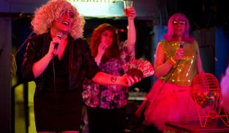 **FILE** In this Sept. 25, 2013 photo, Vanessa LaVoce-Kellie, aka Devyn Reece, left,  performs with Ataraxia Jones, aka Nicholas Dehart, center, and Gingi Vitis, aka Todd Rushing, during Drag Queen Bingo at the Rendezvous bar in Juneau, Alaska. (AP Photo/The Juneau Empire, Michael Penn)