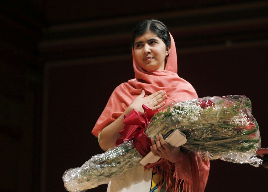 ** FILE ** Malala Yousafzai, gestures after receiving the 2013 Peter J. Gomes Humanitarian Award at Harvard University Friday, Sept. 27, 2013, on the school's campus in Cambridge, Mass. The Pakistani teenager, an advocate for education for girls, survived a Taliban assassination attempt last year on her way home from school. (AP Photo/Jessica Rinaldi)
