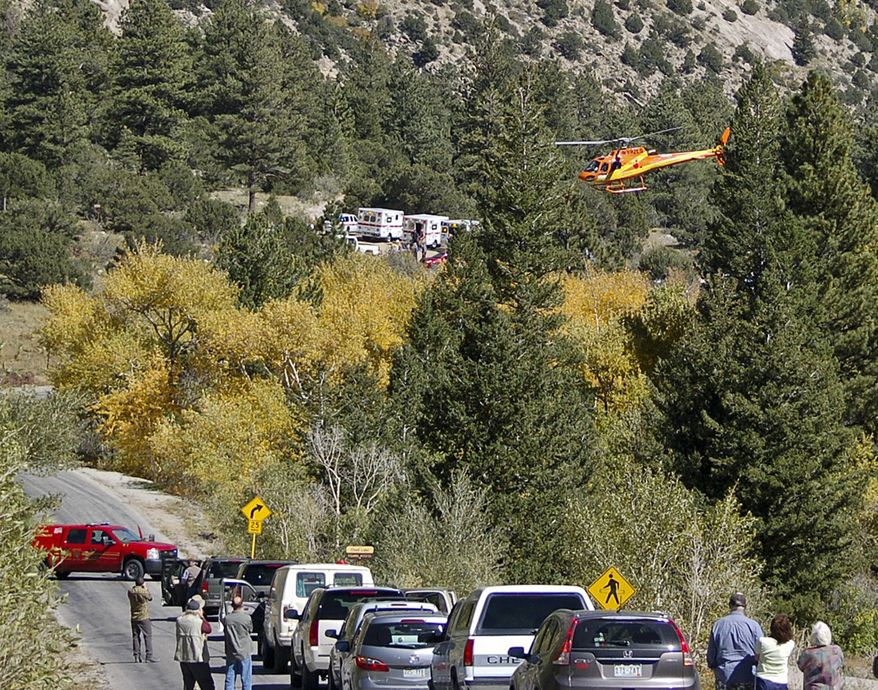 A Flight for Life helicopter rises above backed-up traffic on Monday, Sept. 30, 2013, in south-central Colorado  as emergency personnel work to aid hikers trapped after a rock slide on the trail to Agnes Vaille Falls. (AP Photo/The Mountain Mail, James Redmond)