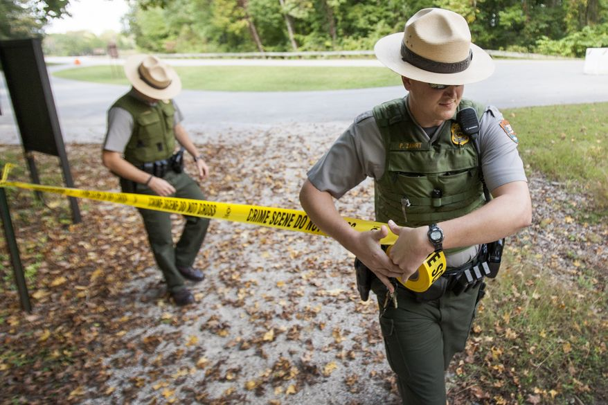 United States Park Rangers Josh Clemons, left, and Peter Zahrt close a trail at Mammoth Cave National Park, Ky. Tuesday, Oct., 1, 2013. National Parks across the country are closed due to the federal government shutdown. (AP Photo/The Daily News, Alex Slitz)