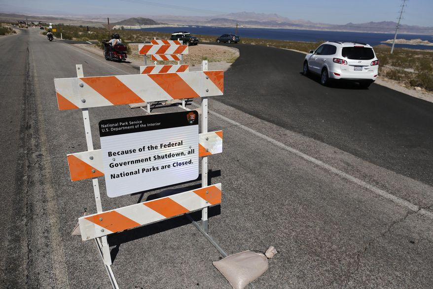 Motorists approaching Lake Mead National Recreation Area drive around a barricade with a sign notifying visitors of the park's closure on Tuesday, Oct. 1, 2013, near Boulder City, Nev. A partial government shutdown, caused by a budget impasse in Congress, has forced the closure of public sites, including the nation's national parks.  (AP Photo/Julie Jacobson)
