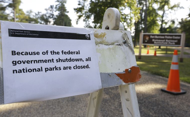 """A sign to the parking lot to the Fort Harrison visitor center on the Richmond National Battlefield Park announces that the park is closed in Richmond, Va., Tuesday, Oct. 1, 2013.   """"Closed"""" signs and barricades sprang up early Tuesday at the Lincoln Memorial, and national parks and many federal workplaces across the country followed suit.  (AP Photo/Steve Helber)"""