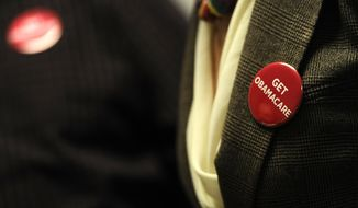 "Associates at Community Health Center wear buttons reading ""Get Obamacare"" during a session to enroll people in the nation's new health insurance system at the Community Health Center, Tuesday, Oct. 1, 2013, in New Britain, Conn. (Associated Press)"