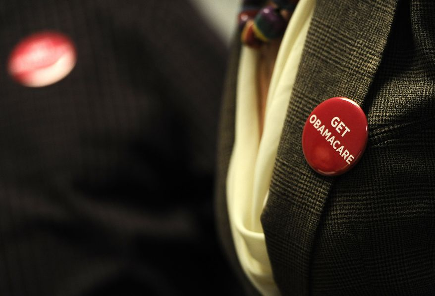 """Associates at Community Health Center wear buttons reading """"Get Obamacare"""" during a session to enroll people in the nation's new health insurance system at the Community Health Center, Tuesday, Oct. 1, 2013, in New Britain, Conn. (Associated Press)"""