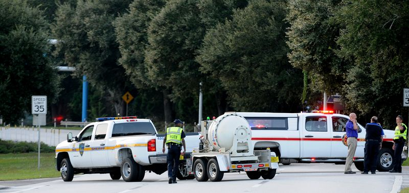 Police block the road to the Jacksonville International Airport terminal as the bomb disposal unit drives by on the right Tuesday, Oct. 1, 2013, in Jacksonville, Fla. The airport was evacuated after authorities found two suspicious packages. (AP Photo/The Florida Times-Union, Bruce Lipsky)