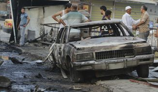 FILE - People inspect the aftermath of a car bomb explosion at a commercial street in Baghdad, Iraq, Sept. 16, 2013. (AP Photo/Hadi Mizban, File)