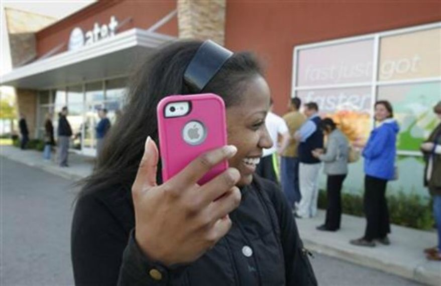 ** FILE ** Western Michigan University student Alenna Brown ,19, leaves with her new iPhone 5 in Kalamazoo, Mich., Sept. 21, 2012. (Associated Press)