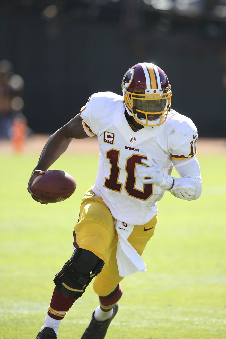 Washington Redskins' Robert Griffin III (10) runs with the ball in the third quarter of an NFL game against the Oakland Raiders in Oakland, California at the O.CO Coliseum on Sunday, Sept. 29, 2013. (AP Photo/David Seelig)