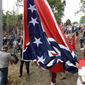 ** FILE ** Virginia Flaggers raise the Confederate battle flag near Interstate 95 in Chester, Va., on Saturday, Sept. 28, 2013. Hundreds gathered in freshly cleared woods for the event, celebrated with a volley fired from the rifles of Confederate re-enactors. (AP Photo/Steve Helber)