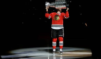 Capitals coach Adam Oates kept his team in the locker room prior to Tuesday's season opener in Chicago as Jonathan Toews (right) and the Blackhawks got to celebrate once again  with the Stanely Cup they won against the Bruins in June. (associated press)