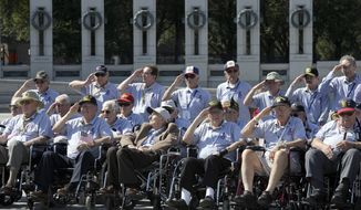 ** FILE ** World War II veterans from the Chicago area salute as they visit the National World War II Memorial in Washington on Wednesday, Oct. 2, 2013. The group came to Washington on an honor flight despite the shutdown of the federal government. (AP Photo/Susan Walsh)
