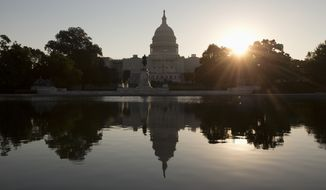 The sun rises behind the Capitol in Washington, Wednesday, Oct. 2, 2013. The political stare-down on Capitol Hill shows no signs of easing, leaving federal government functions _ from informational websites, to national parks, to processing veterans' claims _ in limbo from coast to coast. Lawmakers in both parties ominously suggested the partial shutdown might last for weeks.  (AP Photo/Carolyn Kaster)