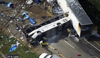 Emergency workers respond to a crash involving a passenger bus, a tractor-trailer and an SUV near Dandridge, Tenn., on Wednesday, Oct. 2, 2013. Authorities said the bus, carrying members of a North Carolina church group, veered across the highway median and crashed into the other vehicles in a fiery wreck that killed several people. (AP Photo/The Knoxville News Sentinel, Paul Efird)