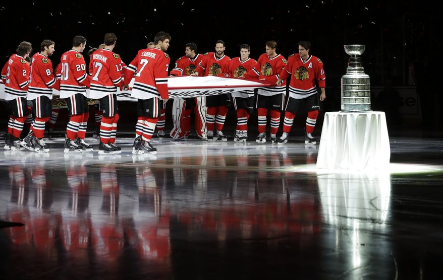The Chicago Blackhawks players carry out the Stanley Cup Championship banner past the Stanley Cup during a ceremony before an NHL hockey game between the Blackhawks and the Washington Capitals on Tuesday, Oct. 1, 2013, in Chicago. (AP Photo/Nam Y. Huh)