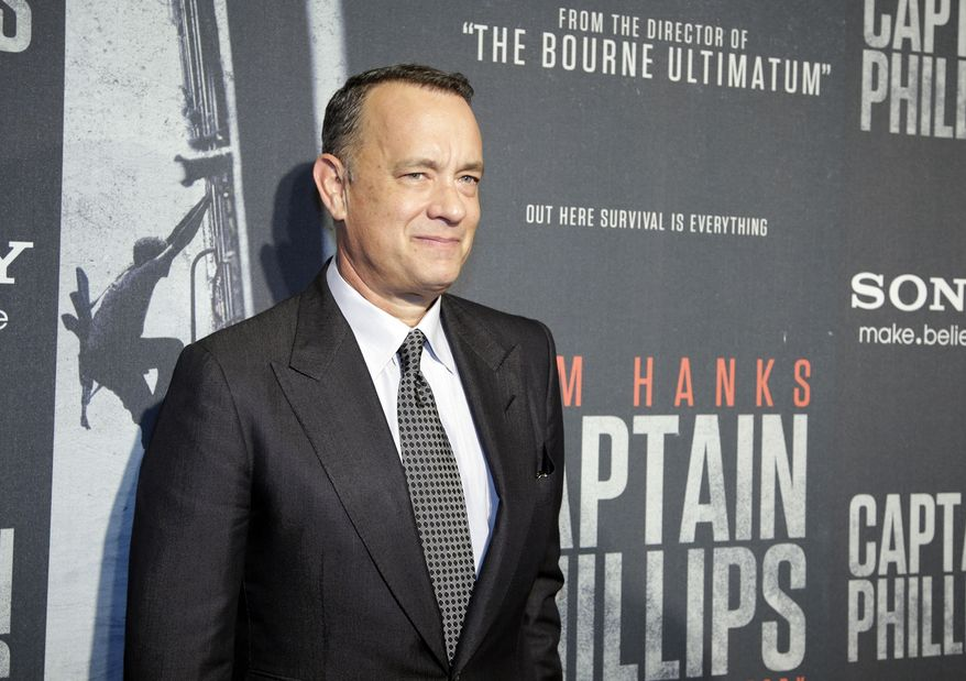 """Tom Hanks poses for photographers as he walks the red carpet at a screening for the movie """"Captain Phillips"""" at the Newseum, Wednesday, Oct. 2, 2013 in Washington. (AP Photo/Alex Brandon)"""