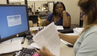 ** FILE ** In this Oct. 1, 2013, file photo, Lillian Ardon, right, a certified application counselor with Harris Health System, helps Vanessa Danielle Cotton, left, with her Affordable Care Act marketplace application in Houston. (AP Photo/David J. Phillip, File)