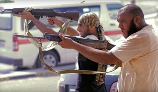 ** FILE ** Libyan rebel fighters in downtown Tripoli, Libya, Aug. 22, 2011. (Associated Press)