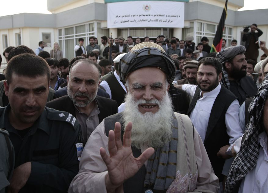 Abdul Rab Rasoul Sayyaf, an influential lawmaker and religious scholar, waves to his supporters after registering his candidacy in next year's presidential election in Kabul, Afghanistan, on Thursday, Oct. 3, 2013. Another former warlord, Ismail Khan, who formerly served as energy and water minister, said he will run for Mr. Sayyaf's first vice presidency in the April 5 vote. (AP Photo/Rahmat Gul)