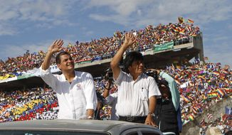 ** FILE ** Ecuador's President Rafael Correa, left, and Bolivia's President Evo Morales wave during a welcome ceremony for Correa in Ivirgarzama, Bolivia, Thursday, Oct. 3, 2013. (AP Photo/Juan Karita)