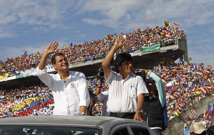 ** FILE ** Ecuador's President Rafael Correa, left, and Bolivia's President Evo Morales wave during a welcome ceremony for Correa in Ivirgarzama, Bolivia, Thursday, Oct. 3, 2013. (AP Photo/Juan Karita)