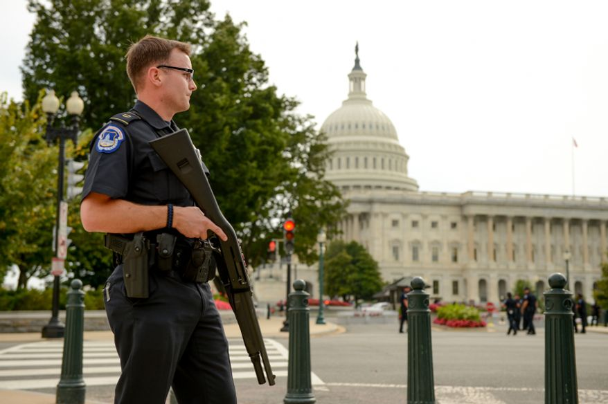 U.S. Capitol Police Officers stand guard in front of the U.S. Capitol Building after a car chase ended in a shootout at 1st Street and Constitution Ave. NE in front of the Hart Office Building, Washington, D.C., Thursday, October 3, 2013. (Andrew Harnik/The Washington Times)