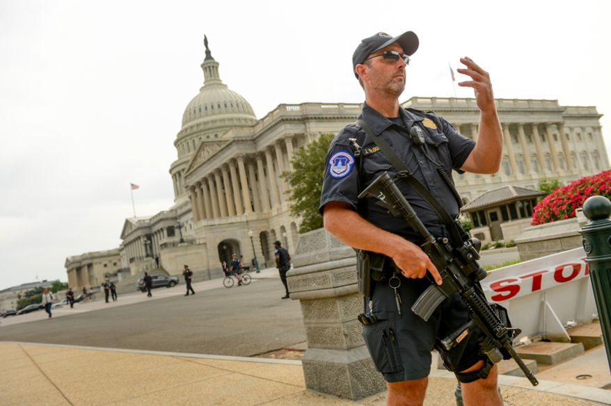 U.S. Capitol Police Officers stand guard in front of the U.S. Capitol Building after shots are fired after a car chase ended at 1st Street and Constitution Ave. NE in front of the Hart Office Building, Washington, D.C., Thursday, October 3, 2013. (Andrew Harnik/The Washington Times)