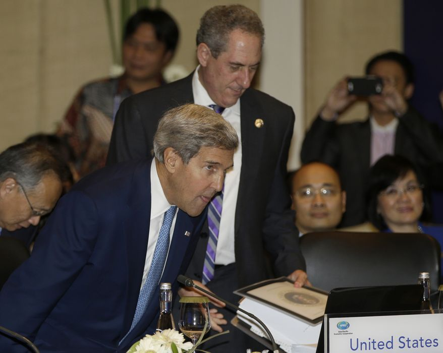 U.S. Secretary of State John Kerry, foreground left, and U.S. Trade Representative Michael Froman, center, take seats prior to the Asia Pacific Economic Cooperation ministerial meeting in Bali, Indonesia, Friday, Oct. 4, 2013. (AP Photo/Dita Alangkara, Pool)