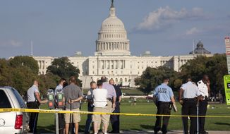 Law enforcement officers are near the scene on the National Mall in Washington, where, according to a fire official, a man set himself on fire Friday, Oct. 4, 2013.  The official said the man was flown by helicopter to a hospital. (AP Photo/J. Scott Applewhite)