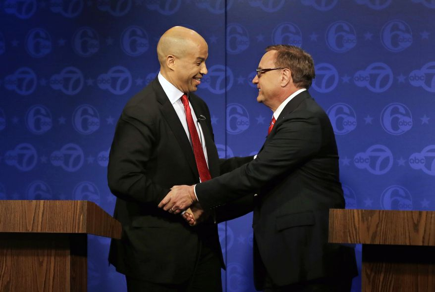 ** FILE ** Democratic Newark Mayor Cory Booker, left, and Republican Steve Lonegan shake hands after their first debate in the U.S. Senate campaign on Friday, Oct. 4, 2013, in Trenton, N.J. The two squared off in the first debate of the campaign with just 12 days to go before the special Senate election. (AP Photo/Mel Evans)